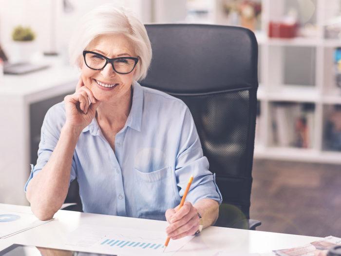 Femme future retraitée assise à un bureau avec des documents sur sa retraite