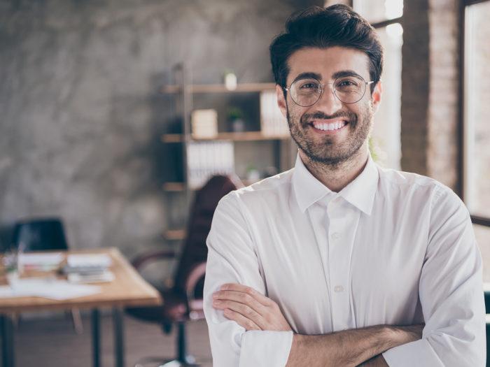 Image d'un jeune entrepreneur debout, les bras croisés, souriant à l'objectif